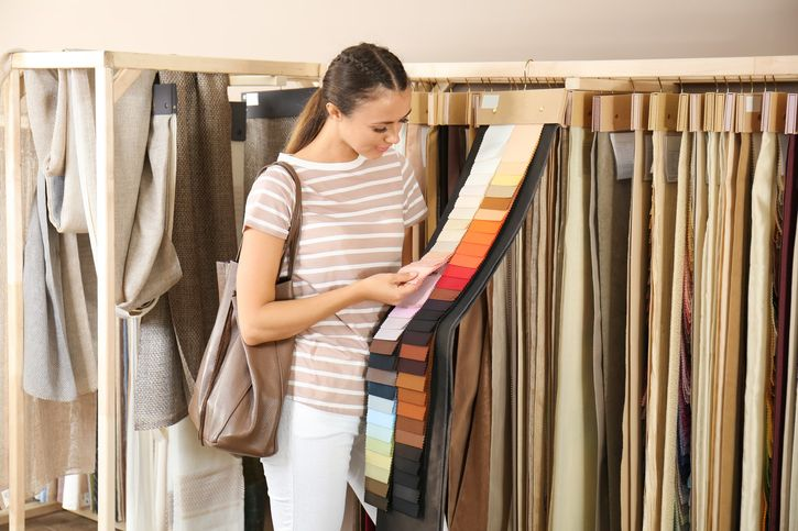A woman choosing a different fabric for her home